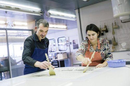 Christophe Ternant, chef de l'atelier Restauration du service technique du département de la Conservation et Anne-Claire Nault, son adjointe, réencollent une affiche du XIXe siècle. (c) Guillaume Murat/BnF